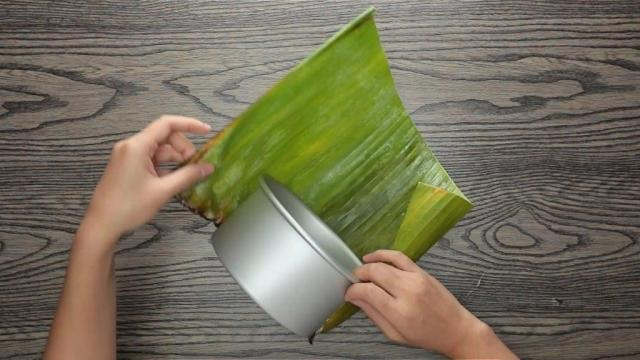 Wrapping banana leaf around a round cake tin
