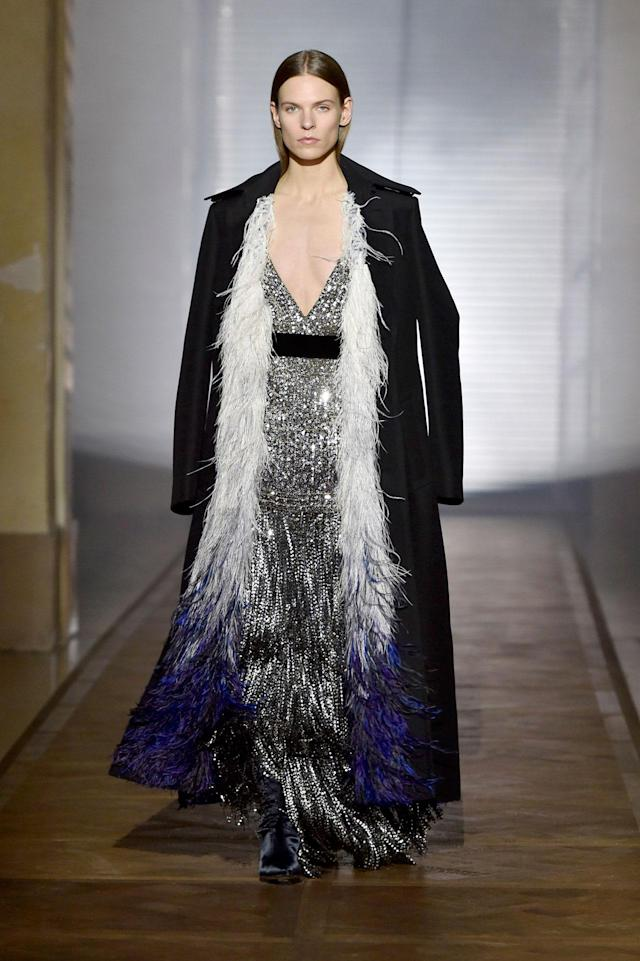 <p>Model wears a silver sequined and beaded fringe gown under a black feather-trimmed coat from the Givenchy SS18 Haute Couture show. (Photo: Getty Images) </p>