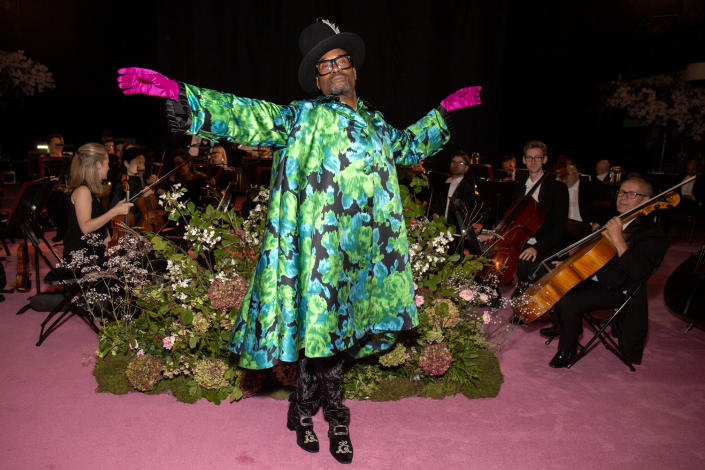 The entertainer had a theatrical look at Richard Quinn's SS20 show wearing a blue and white printed gown with hot pink gloves and a black hat [Photo: Getty Images]