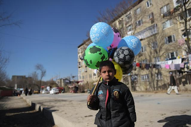 <p>An Afghan child who works as a balloon vendor waits for customers in Kabul on December 6, 2016. (Photo: Shah Marai/ AFP/Getty Images) </p>
