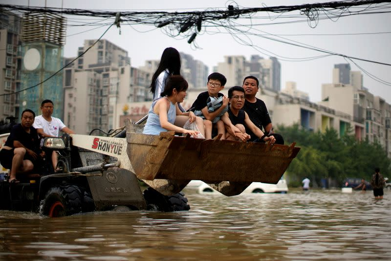 FILE PHOTO: People ride on a front loader as they make their way through floodwaters following heavy rainfall in Zhengzhou