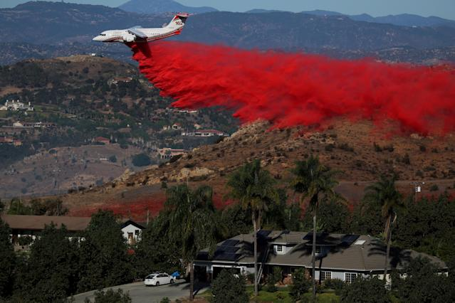 <p>An aircraft drops fire retardant as firefighters take advantage of light winds to attack the Lilac Fire, a fast moving wild fire in Bonsall, Calif., Dec. 8, 2017. (Photo: Mike Blake/Reuters) </p>