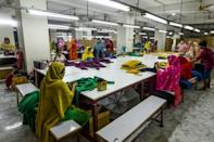 Labourers working hard at a garment factory after its post-virus reopening -- but their future will depend on orders from far afield, notably Spain, one of Europe's worst-hit countries