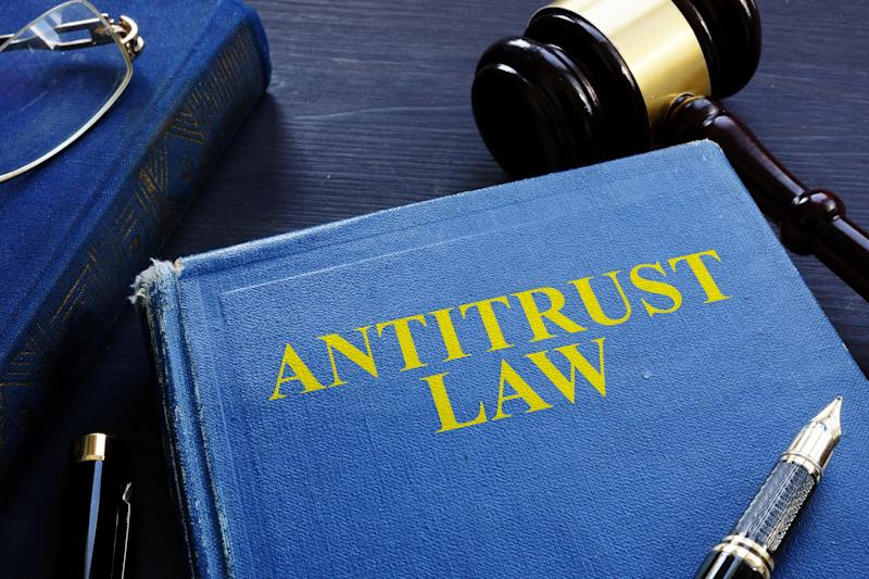 An antitrust law book on a desk with several pens and a gavel.