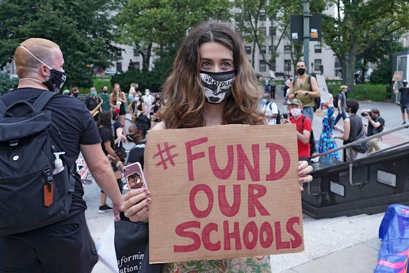 A protester holds a placard that says Fund Our Schools during a demonstration in New York City earlier this month. Several groups, including the United Federation of Teachers, gathered on the National Day of Resistance to protest against reopening of schools as well as for removing police from schools. (Ron Adar/SOPA Images/LightRocket via Getty Images)