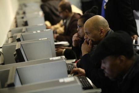 People use computers at a job fair in Detroit