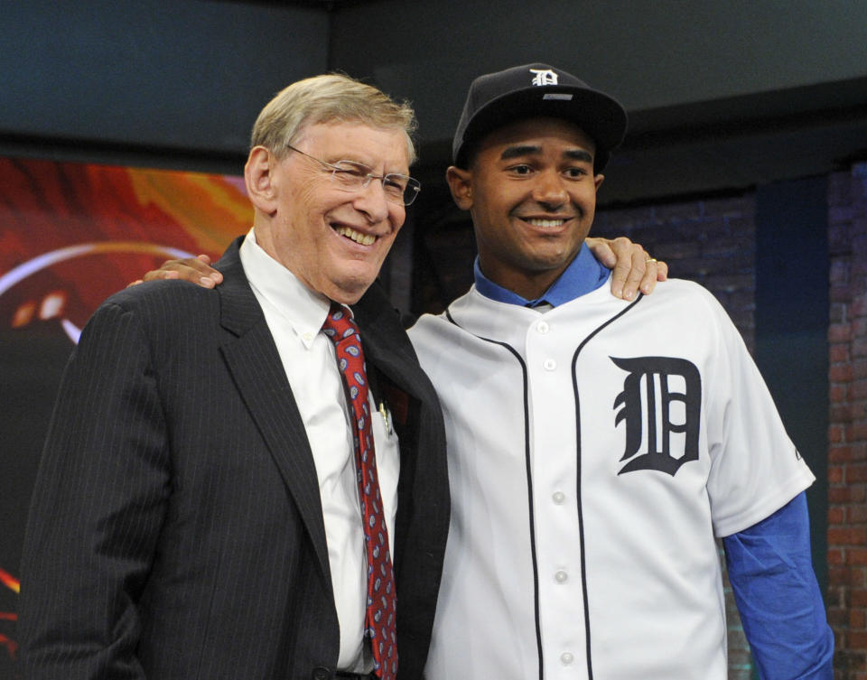 Baseball Commissioner Bud Selig, left, poses with outfielder Derek Hill from Elk Grove High School in Sacramento, California, at the 2014 MLB baseball draft Thursday, June 5, 2014, in Secaucus, N.J. Hill was selected by the Detroit Tigers with the 23rd pick in the first round. (AP Photo/Bill Kostroun)