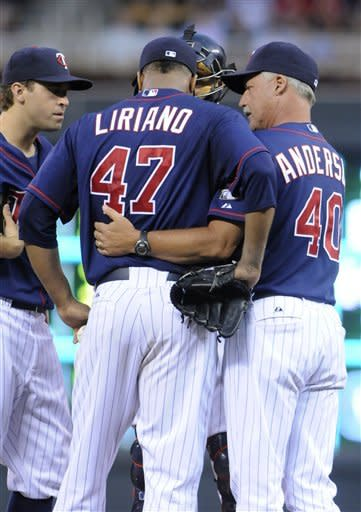 Minnesota Twins pitching coach Rick Anderson, right, talks with pitcher Francisco Liriano after a grand slam by Oakland Athletics' Jonny Gomes in the fourth inning of a baseball game Friday, July 13, 2012 in Minneapolis. At left is shortstop Brian Dozier. (AP Photo/Jim Mone)