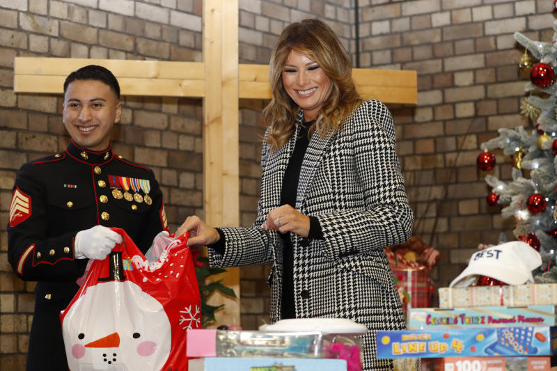 First lady Melania Trump joins local students and U.S. Marines stationed at the U.S. Embassy, wrapping holiday presents to be donated to the Salvation Army, at the Salvation Army Clapton Center in London, Wednesday, Dec. 4, 2019. (AP Photo/Alastair Grant, Pool)