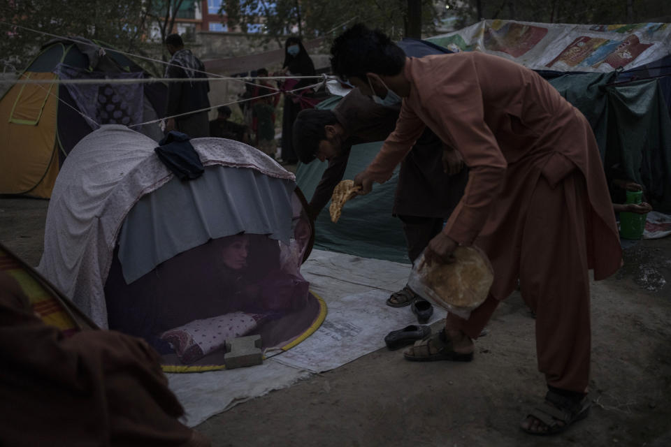 Displaced Afghans distribute food donations at an internally displaced persons camp in Kabul, Afghanistan, Monday, Sept. 13, 2021. (AP Photo/Bernat Armangue)
