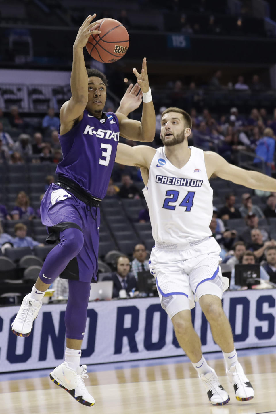 Kansas State's Kamau Stokes (3) drives past Creighton's Mitch Ballock (24) during the first half of a first-round game in the NCAA men's college basketball tournament in Charlotte, N.C., Friday, March 16, 2018. (AP Photo/Gerry Broome)
