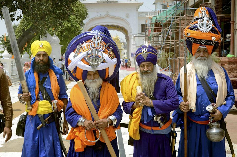 Nihangs or Sikh religious warrior wearing a large turban offer prayers during the eve of 400th birth anniversary of Guru Teg Bahadur Ji, at the Golden Temple in Amritsar on Friday, 30 April 2021.