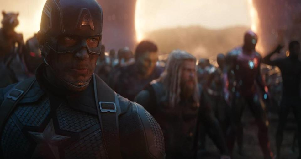 Captain America stands determined with many Avengers standing lined up behind him