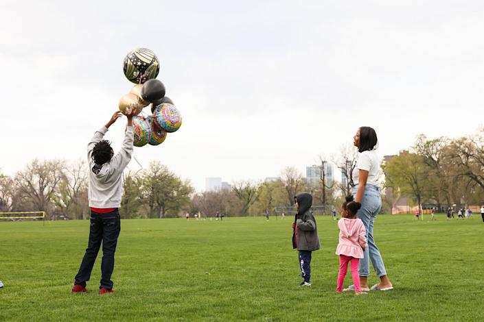 """Nehemiah prepares to release balloons in commemoration of his father while his mother Ashley, his 4-year-old bother, Prince, and 3-year-old sister, Zyla, watch nearby<span class=""""copyright"""">Kevin Mohatt for TIME</span>"""