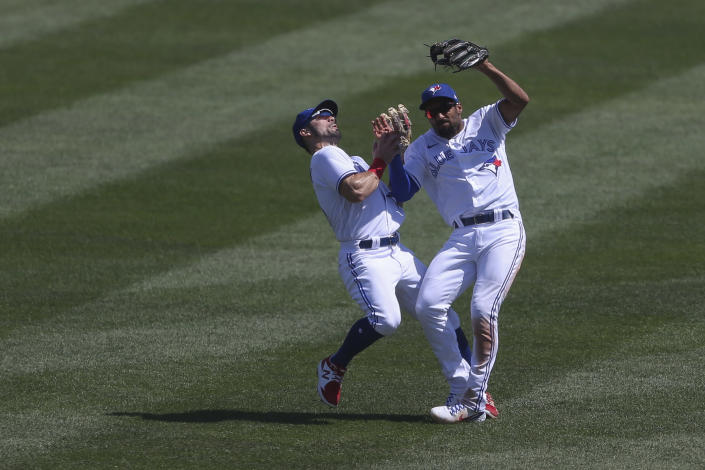 Toronto Blue Jays second baseman Marcus Semien, right, collides with center fielder Randal Grichuk, left, while making a catch during the seventh inning of a baseball game against the Houston Astros in Buffalo, N.Y., Sunday, June 6, 2021. (AP Photo/Joshua Bessex)