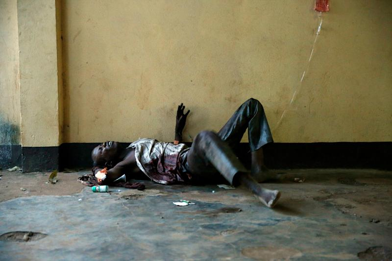 A severely wounded man lies unattended in a Bangui mosque, Bangui, Central African Republic, Thursday, Dec. 5, 2013 following a day-long gun battle between Seleka soldiers and Christian militias. Over 40 bodies, civilian and some military, have been brought for funeral preparations. Gunfire and mortar rounds erupted in the town, leaving scores dead and wounded. To try to put an end to sectarian violence, the UN security council passed a motion allowing French troops to deploy in the country in order to protect civilians and insure security by all necessary means. (AP Photo/Jerome Delay)