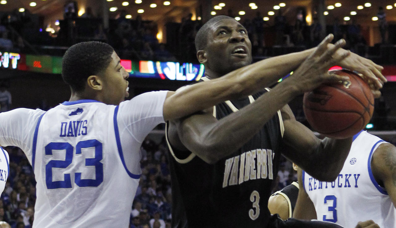 Kentucky forward Anthony Davis (23) fouls Vanderbilt center Festus Ezeli (3) as he tries to block a shot during the first half of an NCAA college basketball game in the championship game of the Southeastern Conference tournament at the New Orleans Arena in New Orleans, Sunday, March 11, 2012. (AP Photo/Gerald Herbert)