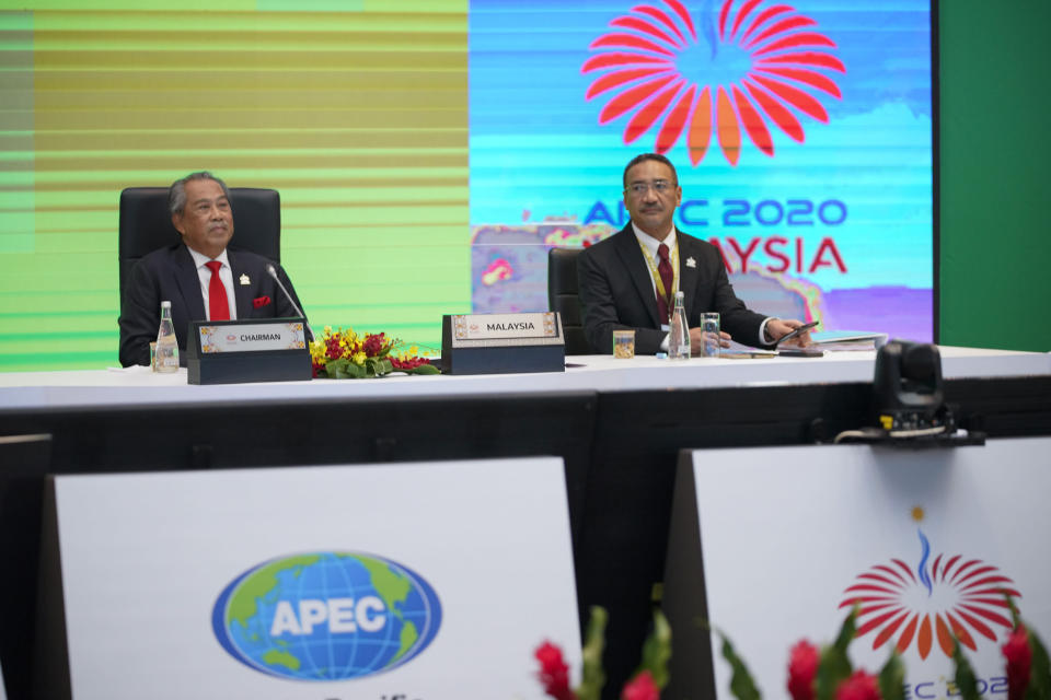 Malaysia's Prime Minister Muhyiddin Yassin, left, and Foreign Minister Hishammuddin Hussein wait for their opening remarks of the first virtual Asia-Pacific Economic Cooperation (APEC) leaders' summit, hosted by Malaysia, in Kuala Lumpur, Malaysia, Friday, Nov. 20, 2020. (AP Photo/Vincent Thian)