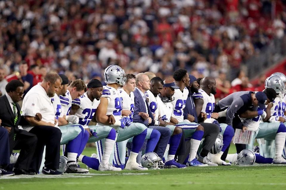 Members of the Dallas Cowboys link arms and kneel during the National Anthem before the start of the NFL game against the Arizona Cardinals at the University of Phoenix Stadium on September 25, 2017 in Glendale, Arizona (AFP Photo/Christian Petersen)