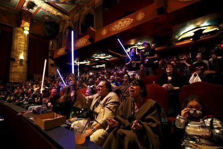 """Moviegoers cheer and wave lightsabers before the first showing of the movie """"Star Wars: The Force Awakens"""" at the TCL Chinese Theatre in Hollywood, California, December 17, 2015. REUTERS/Mario Anzuoni"""