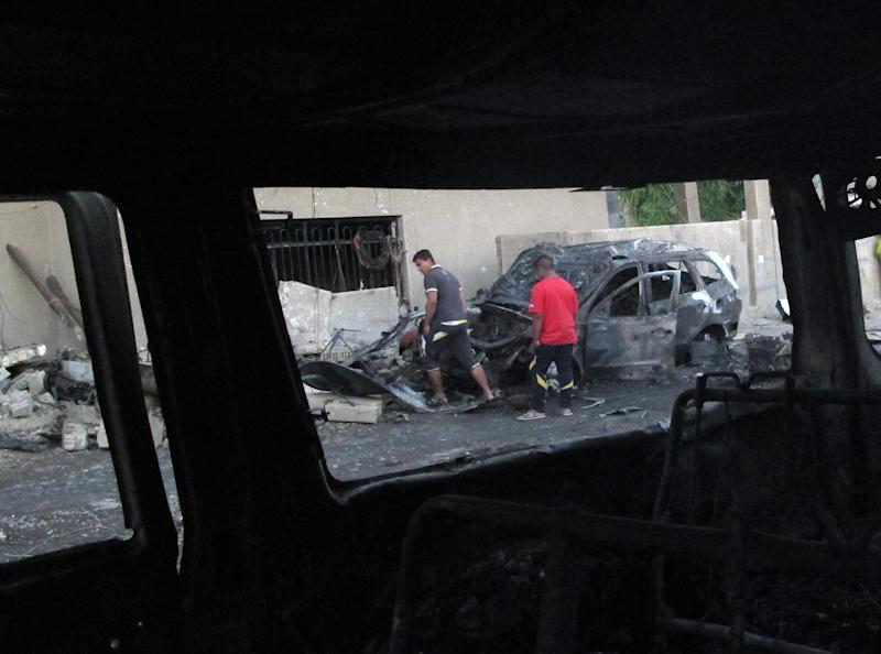 People check a vehicle destroyed in a blast in the Baghdad al-Jadidah district, a mixed area under the control of Shiite militias in Baghdad, Iraq, Monday, Oct. 7, 2013. The attack is the latest in a relentless wave of killing that has made for Iraq's deadliest outburst of violence since 2008. (AP Photo/ Khalid Mohammed)