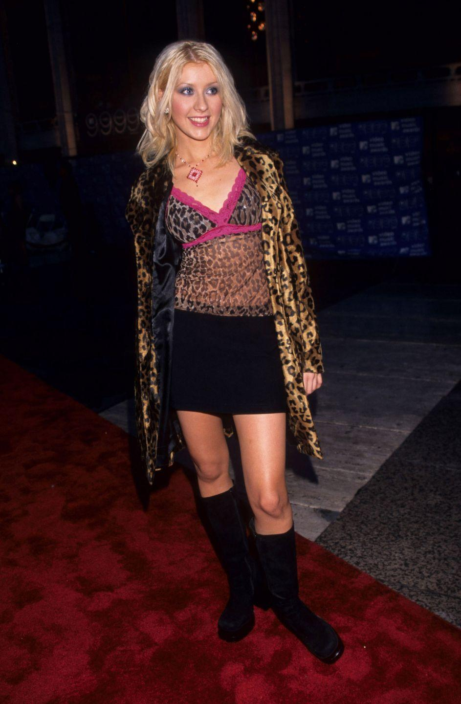 <p>Xtina donned this sheer animal-printed cami with pink lace trim and a matching jacket over a black mini and knee-high boots. </p>