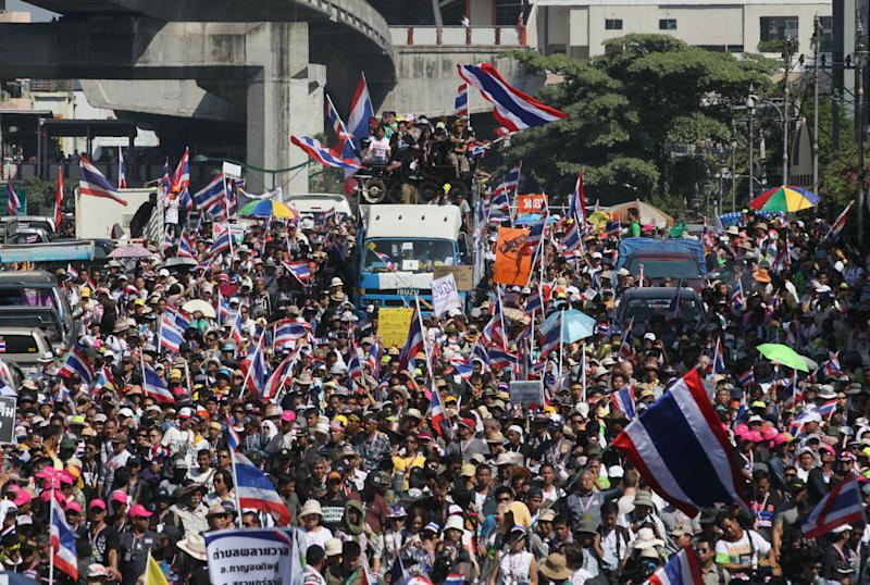 Anti-government protesters with national flags gather for a rally Monday, Jan. 13, 2014, in Bangkok, Thailand. Anti-government protesters took over key intersections in Thailand's capital Monday, halting much of the traffic into Bangkok's central business district as part of a months-long campaign to thwart elections and overthrow the democratically elected prime minister. (AP Photo/Sakchai Lalit)