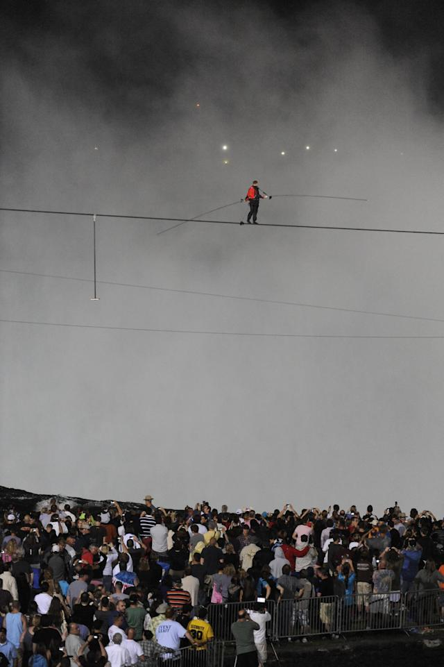 Nik Wallenda walks across Niagara Falls on a tightrope as seen from Niagara Falls, N.Y., Friday, June 15, 2012. Wallenda has finished his attempt to become the first person to walk on a tightrope 1,800 feet across the mist-fogged brink of roaring Niagara Falls. The seventh-generation member of the famed Flying Wallendas had long dreamed of pulling off the stunt, never before attempted. (AP Photo/Gary Wiepert)