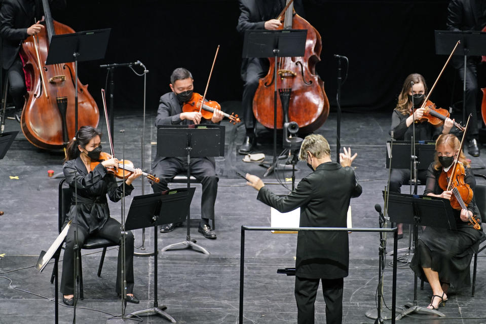 CORRECTS SPELLING OF FIRST NAME TO ESA INSTEAD OF ESSA - Esa-Pekka Salonen, music director of the San Francisco Symphony and principal conductor of London's Philharmonia Orchestra, leads members of the New York Philharmonic as a guest conductor before an audience of 150 concertgoers at The Shed in Hudson Yards, Wednesday, April 14, 2021, in New York. It was the first time since March 10, 2020, that the entire orchestra performed together in front of a live audience. (AP Photo/Kathy Willens)