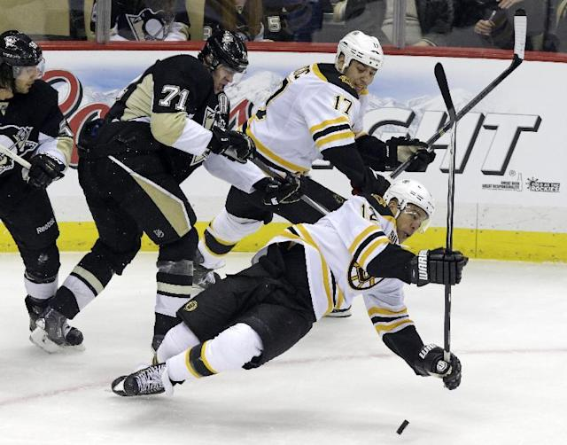 Boston Bruins' Jarome Iginla (12) falls to the ice after colliding with Pittsburgh Penguins' Kris Letang, left, in front of Penguins' Evgeni Malkin (71) and Bruins' Milan Lucic (17) during the first period of an NHL hockey game in Pittsburgh Wednesday, Oct. 30, 2013. (AP Photo/Gene J. Puskar)