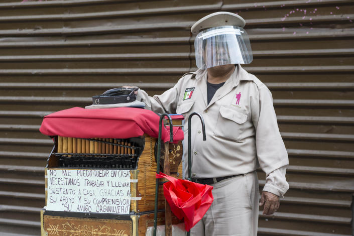 A barrel organ player wearing a face shield as a precaution against the spread of the new coronavirus, hopes for donations in Mexico City, Saturday, May 16, 2020. (AP Photo/Christian Palma)