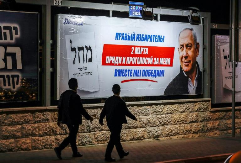 """Ultra-Orthodox Jewish men walk past an election billboard in Jerusalem showing Israeli Prime Minister Benjamin Netanyahu and text in Russian reading """"Come vote for me, together we will win!"""" (AFP Photo/AHMAD GHARABLI)"""