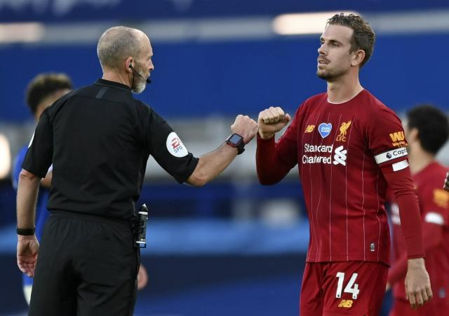Liverpool's Jordan Henderson greets referee Mike Dean at the end of the English Premier League soccer match between Everton and Liverpool at Goodison Park in Liverpool, England, Sunday, June 21, 2020. (AP photo/Shaun Botterill, Pool)