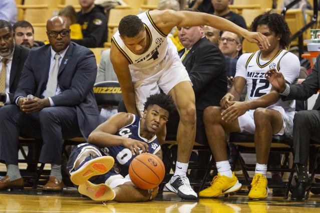 Charleston Southern's Travis Anderson, bottom, saves a ball from going into the Missouri bench in front of Missouri's Javon Pickett, top, during the second half of an NCAA college basketball game Tuesday, Dec. 3, 2019, in Columbia, Mo. Charleston Southern won the game 68-60. (AP Photo/L.G. Patterson)