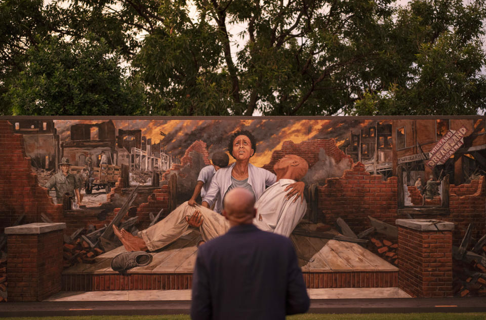 FILE - In this Thursday, May 27, 2021 file photo, Darius Kirk looks at a mural depicting the Tulsa Race Massacre in the historic Greenwood neighborhood ahead of centennial commemorations of the massacre in Tulsa, Okla. The horror and violence visited upon Tulsa's Black community in 1921 didn't become part of the American story. Instead, it was pushed down, unremembered and untaught until efforts decades later started bringing it into the light. (AP Photo/John Locher, File)