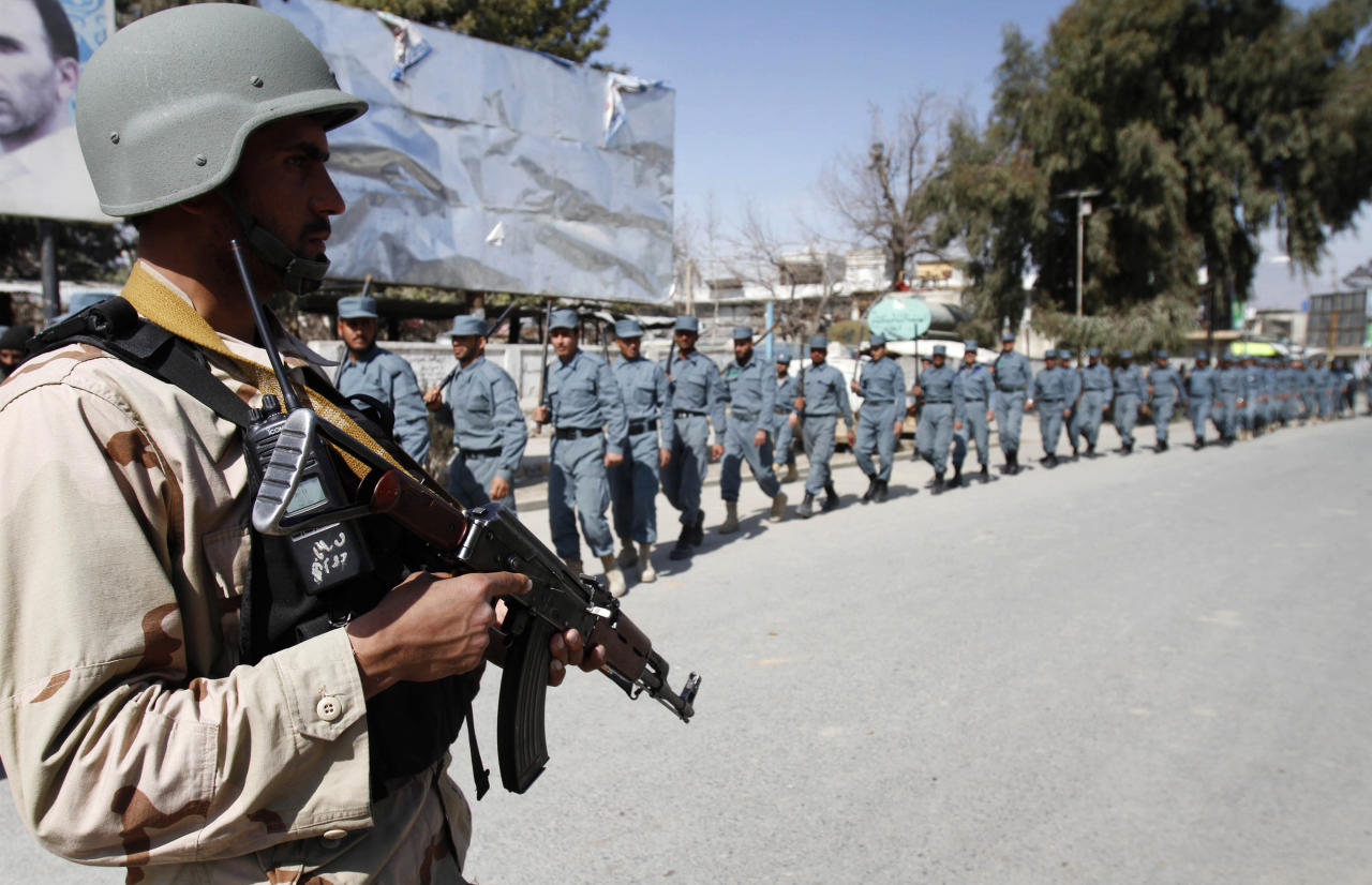 Afghan policemen march towards an anti-U.S. demonstration in Mehterlam, Laghman province east of Kabul, Afghanistan, Saturday, Feb. 25, 2012. Protesters threw rocks at police, government buildings and a U.N. office in eastern Afghanistan on Saturday, kicking off a fifth day of riots sparked by the burning of Qurans at a U.S. base, officials said. (AP Photo/Rahmat Gul)
