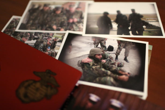 """A group of old photos laying on Mansoor Shams' desk in his Baltimore home on Friday, Aug. 13, 2021, show him as a young Marine during his service from 2000-2004. After 9/11, Shams was called names like """"Taliban,"""" """"terrorist"""" and """"Osama bin Laden"""" by some of his fellow Marines. In recent years, Shams has used his identity as both a Muslim and a former Marine to dispel misconceptions about Islam. (AP Photo/Jessie Wardarski)"""
