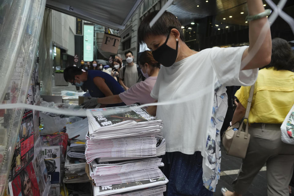 A vender adjusts a stack of last issue of Apple Daily at a newspaper booth at a downtown street in Hong Kong, Thursday, June 24, 2021. Hong Kong's sole remaining pro-democracy newspaper has published its last edition. Apple Daily was forced to shut down Thursday after five editors and executives were arrested and millions of dollars in its assets were frozen as part of China's increasing crackdown on dissent in the semi-autonomous city. (AP Photo/Vincent Yu)