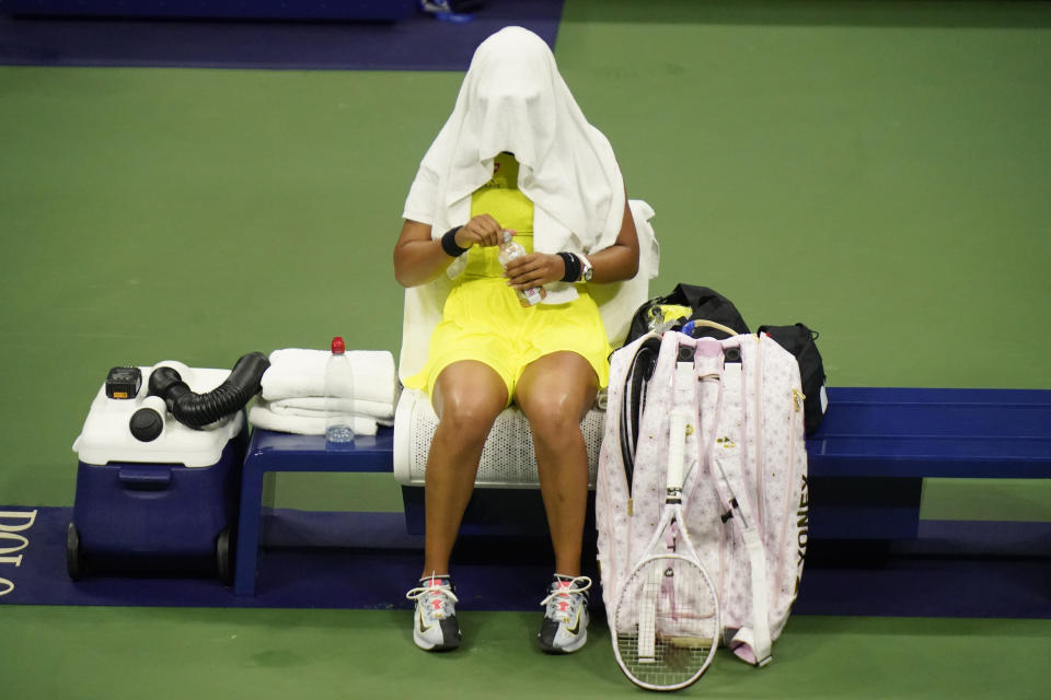 Naomi Osaka, of Japan, covers her head between games against Leylah Fernandez, of Canada, at the third round of the US Open tennis championships, Friday, Sept. 3, 2021, in New York. (AP Photo/Frank Franklin II)