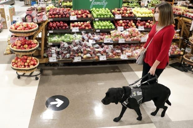 Shelley Adams, with Rookie, showing that guide dogs can also misread directional signs in a retail shop.