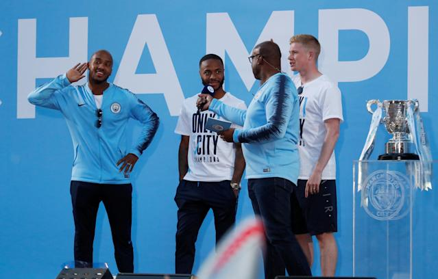 Soccer Football - Premier League - Manchester City Premier League Title Winners Parade - Manchester, Britain - May 14, 2018 Manchester City's Fabian Delph, Raheem Sterling and Kevin De Bruyne on stage during the parade Action Images via Reuters/Andrew Boyers