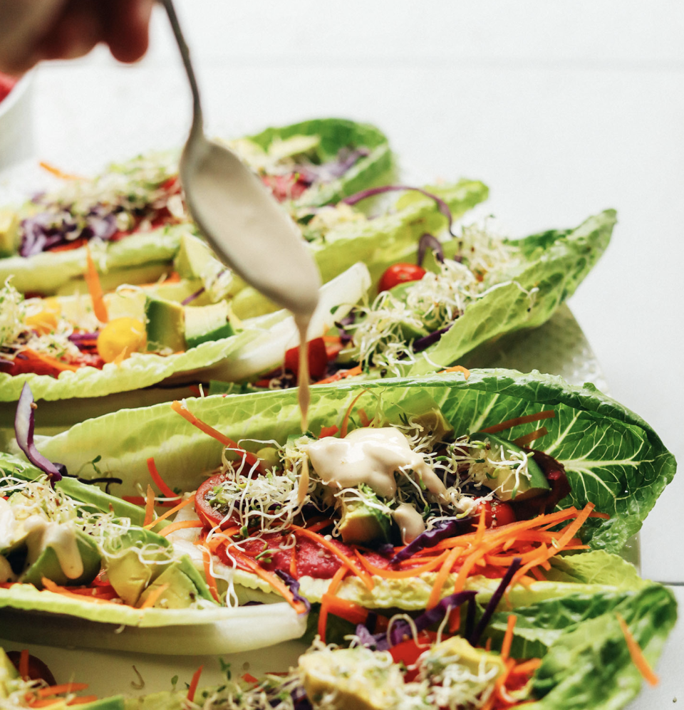 """<p>These 15-minute taco boats are the perfect appetizers to serve when looking to impress your guests with a creative and pretty dish. Drizzle the lettuce cups in un-roasted tahini sauce and homemade hummus for a creamy, picture-perfect finish. <br><br><a class=""""link rapid-noclick-resp"""" href=""""https://minimalistbaker.com/rainbow-raw-maine-taco-boats/#wprm-recipe-container-34687"""" rel=""""nofollow noopener"""" target=""""_blank"""" data-ylk=""""slk:Get the recipe"""">Get the recipe</a><br><br><em>Per three taco boats: 314 cal, 23.6 g fat (4 g saturated fat), 23.2 g carbs, 6.2 g sugar, 166 mg sodium, 9.3 g fiber, 8 g protein</em></p>"""