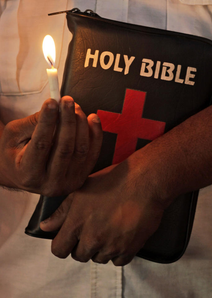 An Indian Christian holding a candle and a bible prays at a church on Good Friday in Ahmadabad, India, Friday, April 6, 2012. Christians around the world are marking the Easter Holy Week. (AP Photo/Ajit Solanki)
