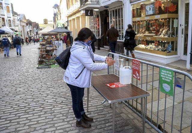 A lady uses hand sanitiser in Guildford, Surrey