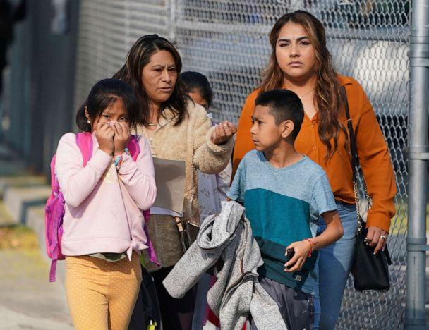 PHOTO: A girl covers her mouth and nose as parents and children leave school after jet fuel was dumped on Park Avenue Elementary School in Cudahy, Calif., Jan. 14, 2020. (Scott Varley/The Orange County Register via AP)