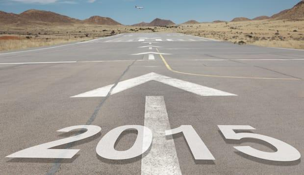 Date numbers 2015 hovering on airport runway with direction markings and mountains in the background