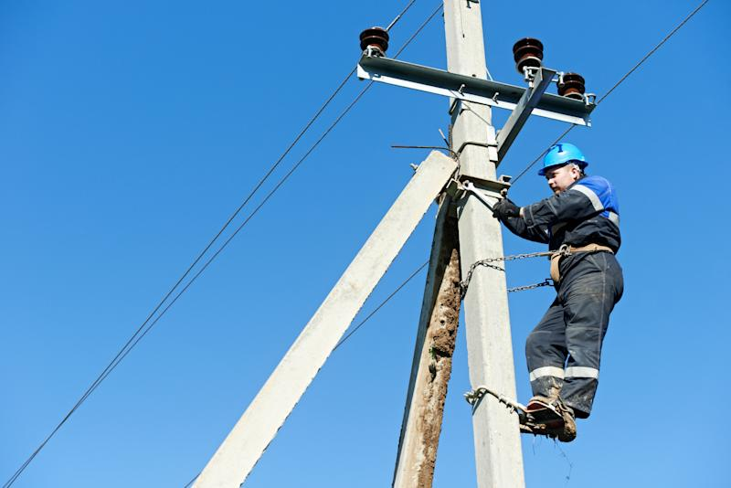 A man working atop an electric pole