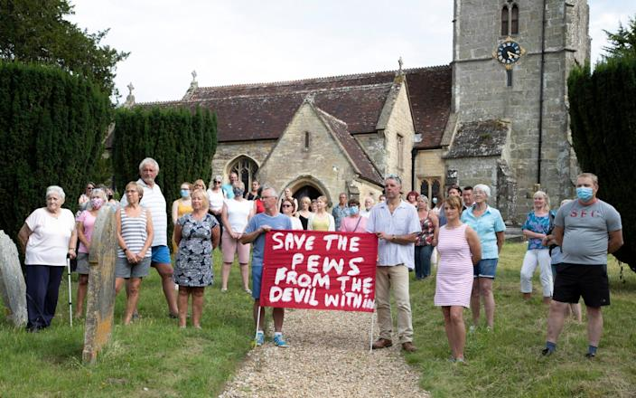 Parishioners gather to protest in the grounds of the Grade II listed St Andrew's Church in the Dorset village of Okeford Fitzpaine - BNPS