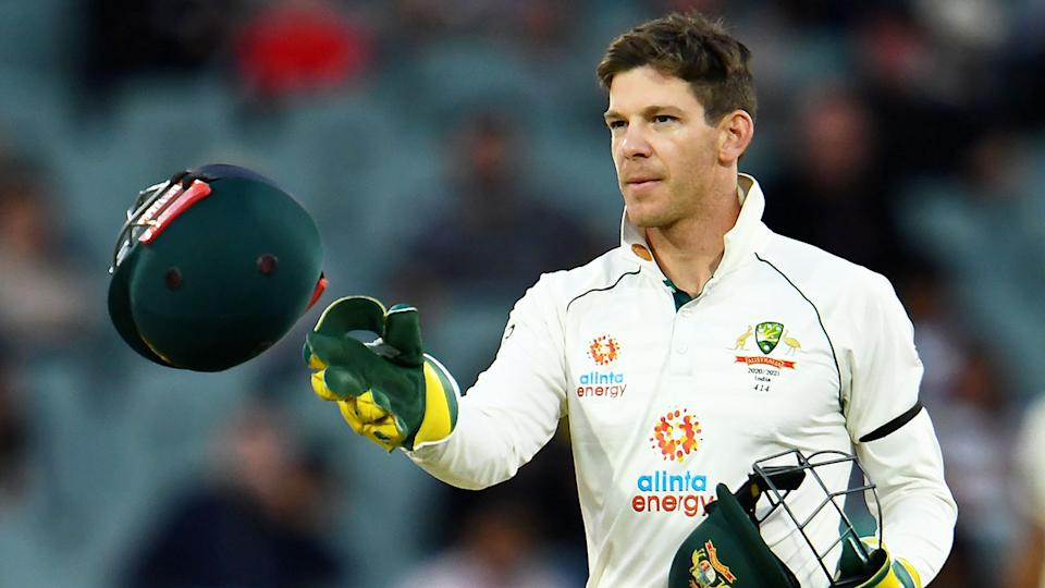 Tim Paine is seen here tossing a helmet to a teammate during the first Test against India.