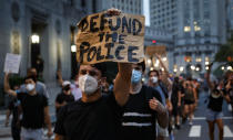 "FILE - This photo from Thursday July 30, 2020, shows a demonstrator holding a sign that reads ""Defund the police"" during a protest march in New York. The chaos unleashed in 2020, amid the coronavirus pandemic, has created space for different voices to speak, for different conversations to be had and for different questions to be asked. (AP Photo/John Minchillo, File)"